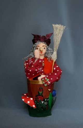 Doll gift porcelain. Baba Yaga in a mortar. Fairy tale character.