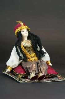 Doll gift porcelain. Scheherazade sitting on the carpet. Fairy tale character.