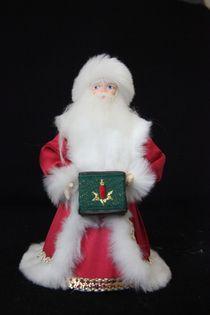 Porcelain souvenir doll. Santa Claus with presents. Fairytale character.