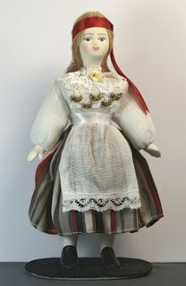 Doll gift. The Estonian girl in national costume with a ribbon on his head.