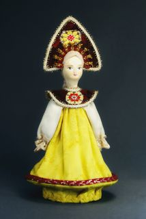 Doll gift porcelain. Girl in Russian costume holiday.