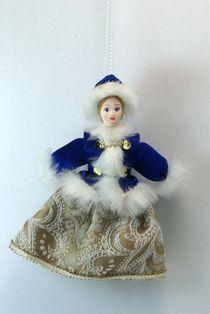 Doll pendant souvenir porcelain. Girl in winter clothes.