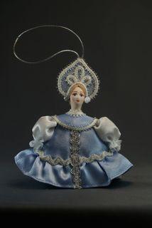 Doll pendant souvenir porcelain. Girl in a summer dress with a shuttlecock.