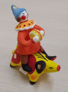 A buffoon on a yellow pig with an accordion, Dymkovo clay toy