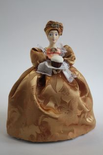 Doll gift porcelain. The merchant's wife with bread-salt. The late 19th century and early 20th century. Russia. The doll on the teapot.