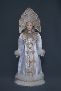 Porcelain souvenir doll. Snow Maiden in a white fur coat and carved kokoshnik. Fairytale character.