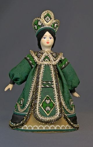 Doll gift porcelain. Girl in Russian folk costume and a crown.